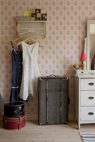 Old suitcases used for storage below vintage dresses hung from coat rack