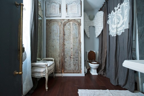Toilet, decorated walls and curtain in vintage-style bathroom