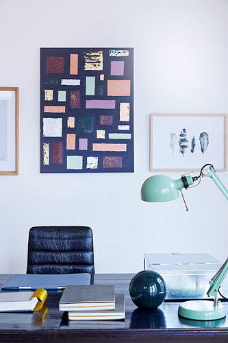 Mint-green reading lamp on dark desk with black leather chair below picture on wall