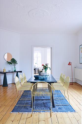 Esszimmer mit dunklem Tisch und leichten, goldfarbenen Metallstühlen in Altbauwohnung
