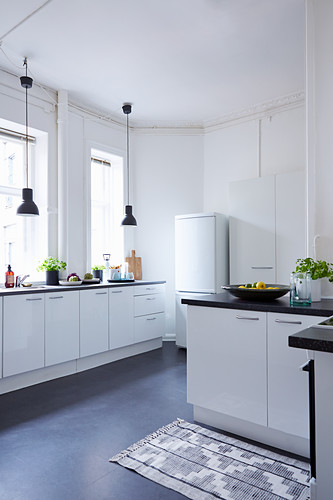 Black pendant lamps in front of windows in white fitted kitchen
