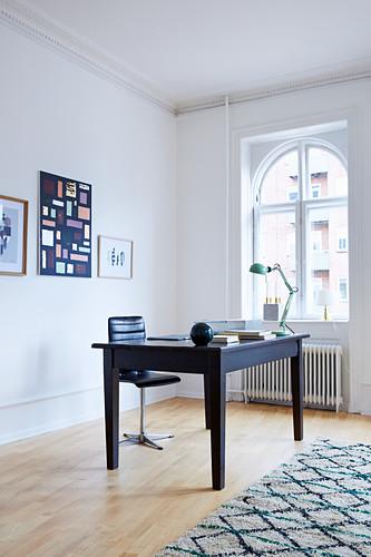 Dunkler Schreibtisch und schwarzer Lederstuhl vor Rundbogenfenster