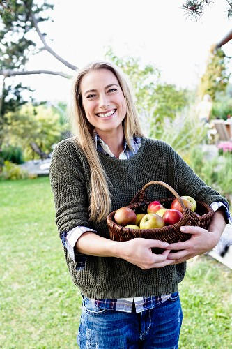 A blonde woman with a basket of fresh apples in a garden