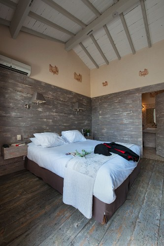 Bedroom with rustic boards on floor and walls