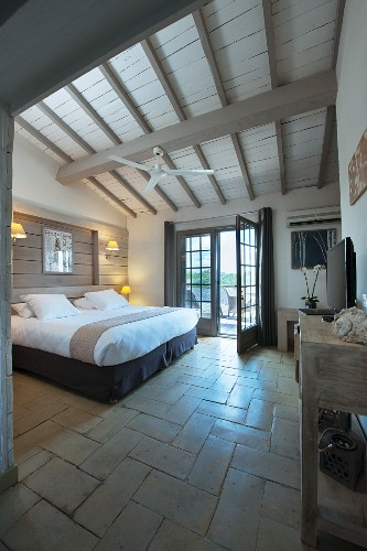 Stone floor and wood-beamed ceiling in rustic bedroom