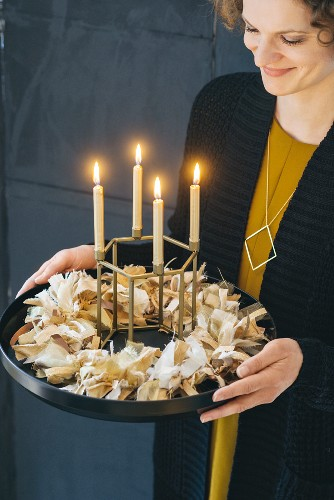 Woman holding Advent wreath hand-made from fabric remnants and four lit candles