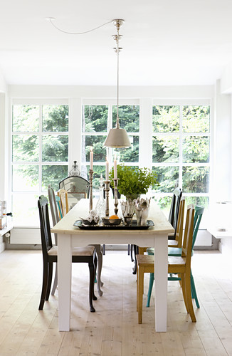 Verschiedene bunte Stühle am Esstisch vor großem Sprossenfenster