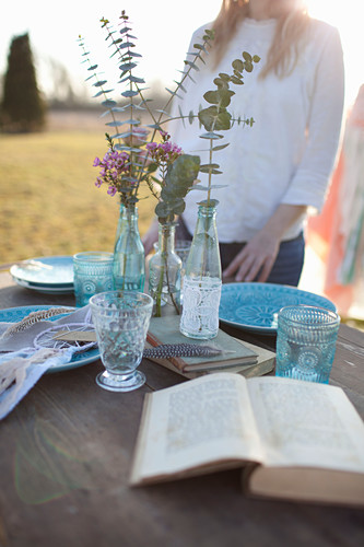 Woman standing next to romantically set table with open book