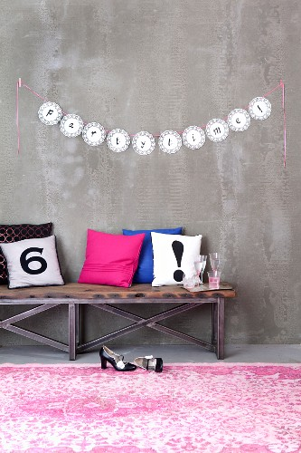 Letters written on garland of doilies decorating wall for party