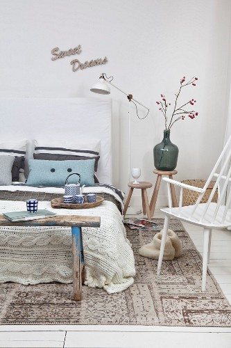 Vintage wooden bench and knitted blanket in bedroom