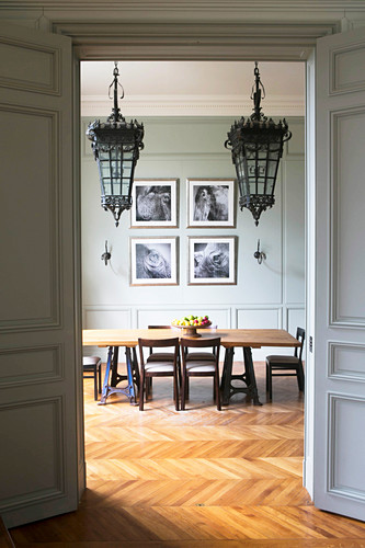 View through open double doors into dining room with antique ceiling lamps