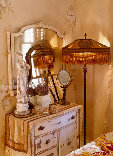 Old standard lamp with fringed shade next to shabby-chic chest of drawers