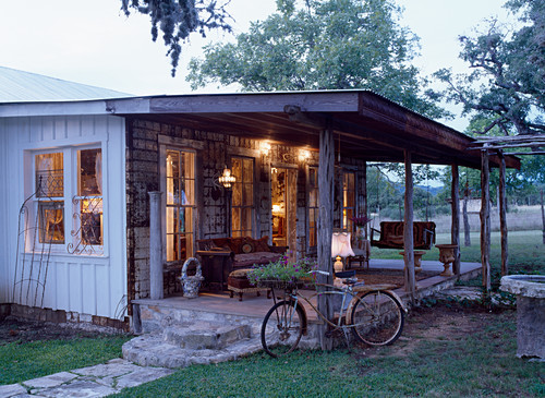 Bicycle leaning against illuminated veranda of wooden cabin