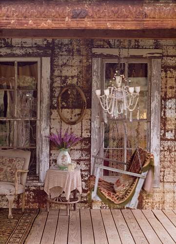 Rocking bench on veranda of old house with melancholy charm