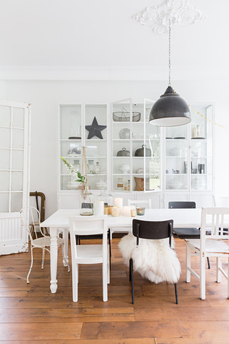 Various chairs around dining table in front of display cabinet