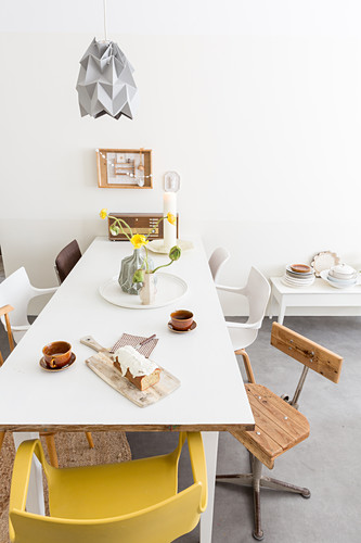Various chairs around coffee and cake on white table