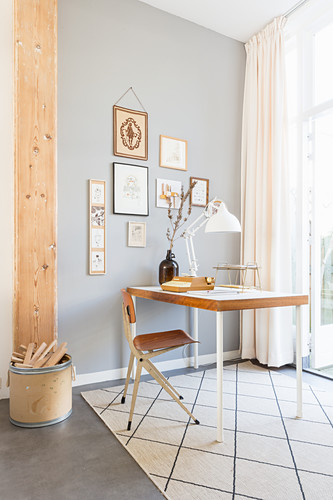 Gallery of pictures on grey wall above retro desk