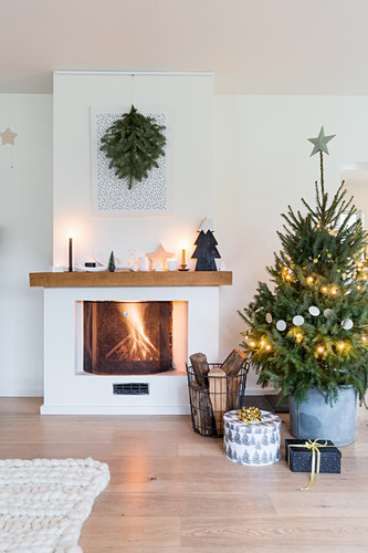 Presents under Christmas tree next to fire in fireplace