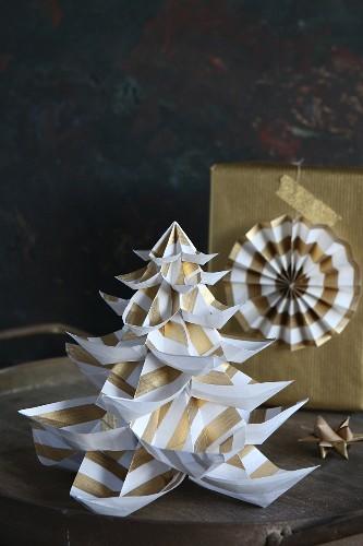 Selbstgebastelter Tannenbaum aus Papier, dahinter Geschenk in goldfarbenem Papier