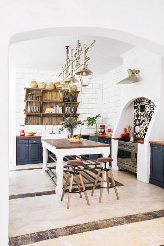 Large table and bar stools in centre of Mediterranean kitchen