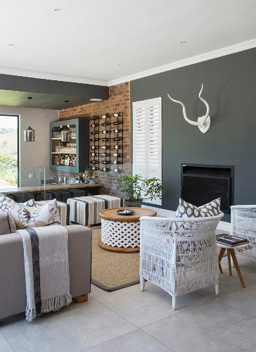 Fireplace in lounge area and brick wall in kitchen area separated by glass half-height partition