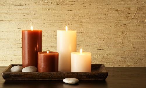Braune und beige Kerzen auf einem eckigen Holztablett