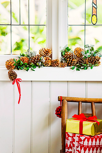 Garland of cones and leaf branches on the window ledge