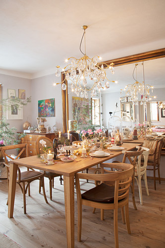 Set table and various chairs next to mirrored wall