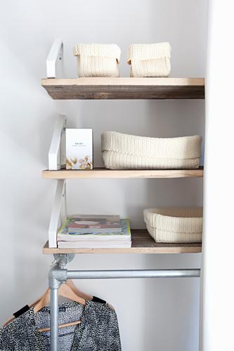 Storage baskets on shelves above clothes rail