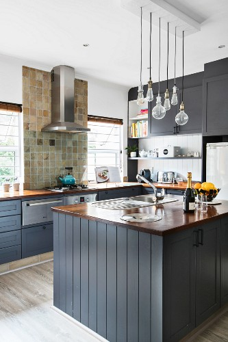 Island counter in American country-house kitchen with grey cupboards