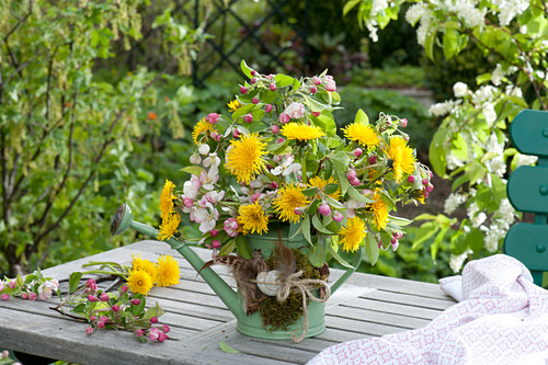 Spring bouquet made of malus (apple) branches and taraxacum