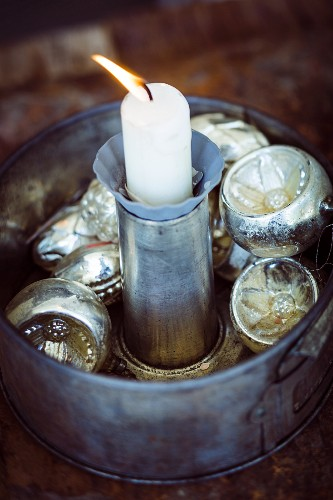 Rustic Christmas arrangement of silver baubles and candle in old cake tin