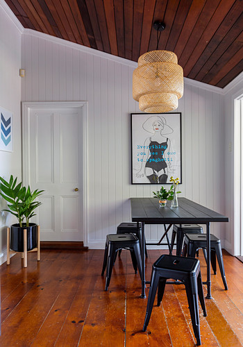 Black metal stools around the dining table against a white plank wall