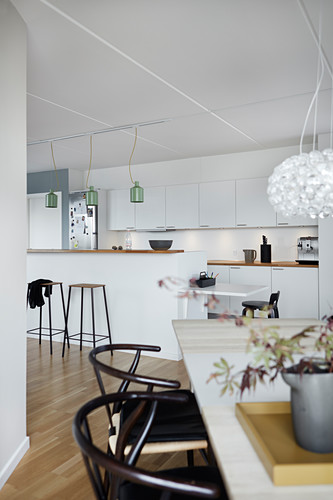 View across dining table into open-plan kitchen with half-height partition wall