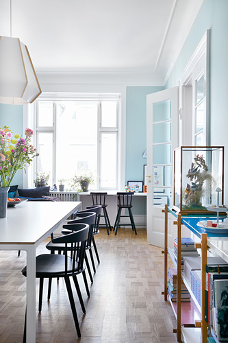 Dining room with pale blue walls in period apartment