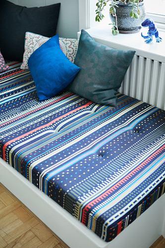 Patterned mattress on day bed below window