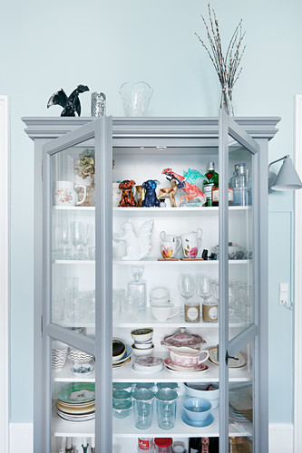 Collection of crockery and glasses in grey display case
