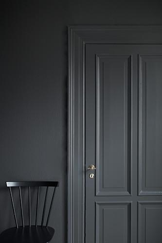 Schwarzer Stuhl vor grauer Wand und grauer Kassettentür