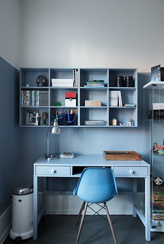 Shelves mounted on two-tone wall above desk