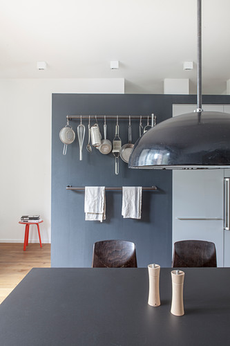 Black table in open-plan kitchen with hook rails mounted on grey wall