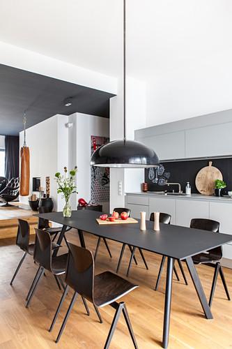Black, modern dining set in open-plan kitchen of designer loft apartment