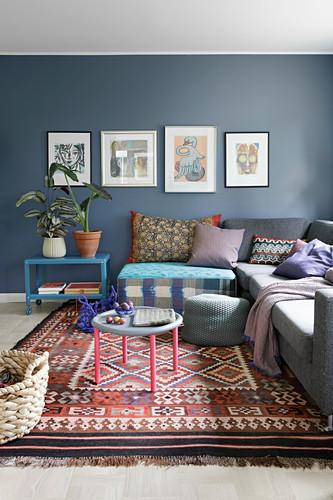 In Reihe gehängte Bilder an blauer Wand im Wohnzimmer mit Ethnoflair