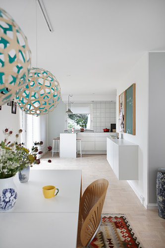 View from dining room into open-plan kitchen entirely in white
