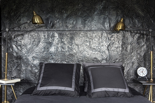Double bed against black relief wall with gilt bedside lamps