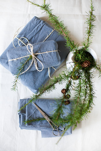 Larch twigs in white jug and gifts wrapped in blue fabric