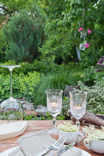 Tealights in wine glasses on set table in garden