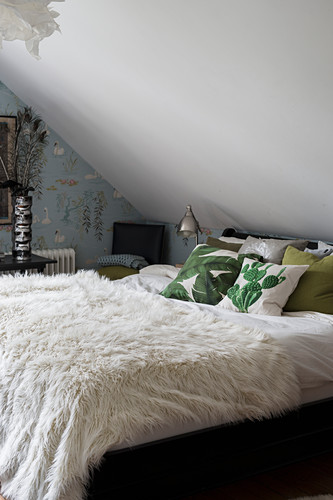 White furry blanket and leaf-patterned scatter cushions on bed below sloping ceiling