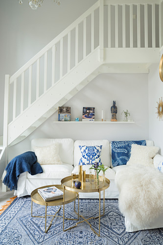 White couch with scatter cushions and set of round tray tables below staircase