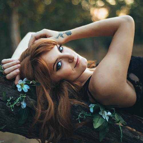 Red-haired woman with tattoo lying on tree branch