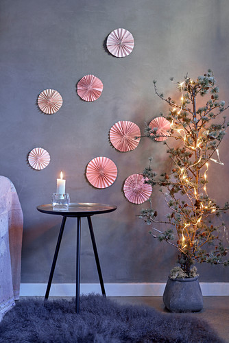 Christmas arrangement of pink paper rosettes on grey wall